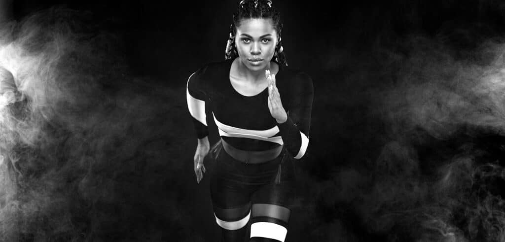Strong,Athletic,Woman,Sprinter,,Running,On,Black,Background